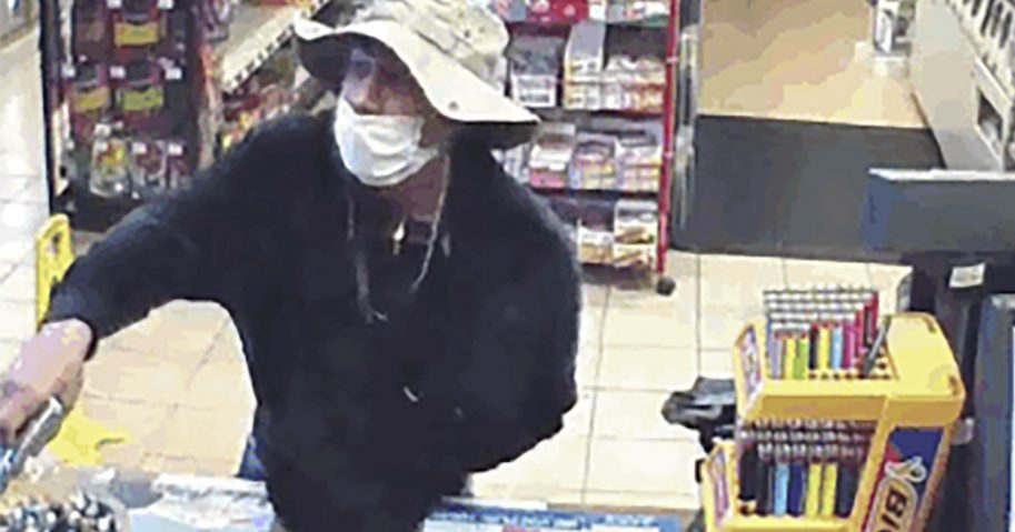 This March 26, 2020, image from surveillance video shows a man, believed to be William Rosario Lopez wearing a surgical mask, with a gun in a Connecticut convenience store. Just how many criminals are taking advantage of the pandemic to commit crimes is impossible to estimate, but law enforcement officials have no doubt that the numbers are climbing. Reports are starting to pop up across the country, as well as in other parts of the world of crimes that were pulled off in no small part because so many of us are wearing masks.