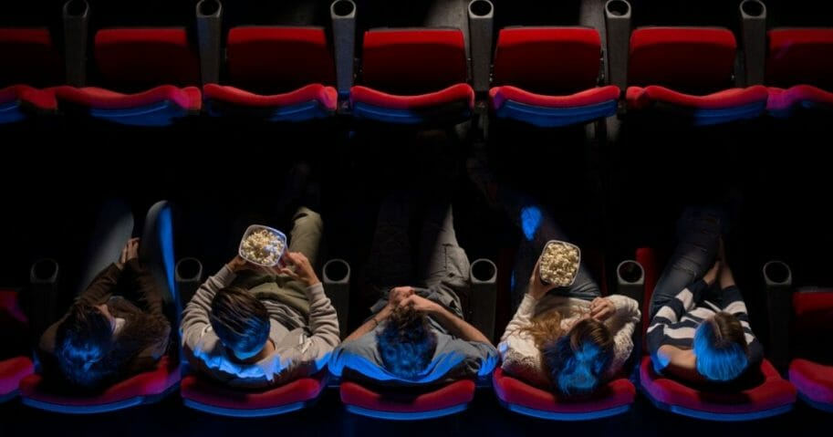People sit in a movie theater in the stock image above.