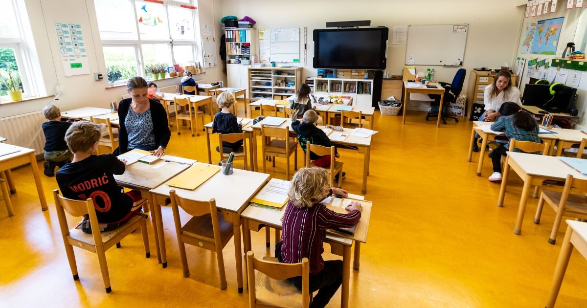 A teacher teaches a class in a classroom at a elementary school