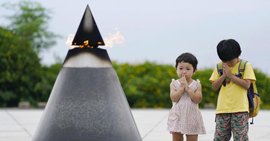 "Children pray in front of the ""Peace of Fire"" at the Peace Memorial Park in Itoman, Okinawa, Japan, on June 23, 2020, 75 years after the Battle of Okinawa."