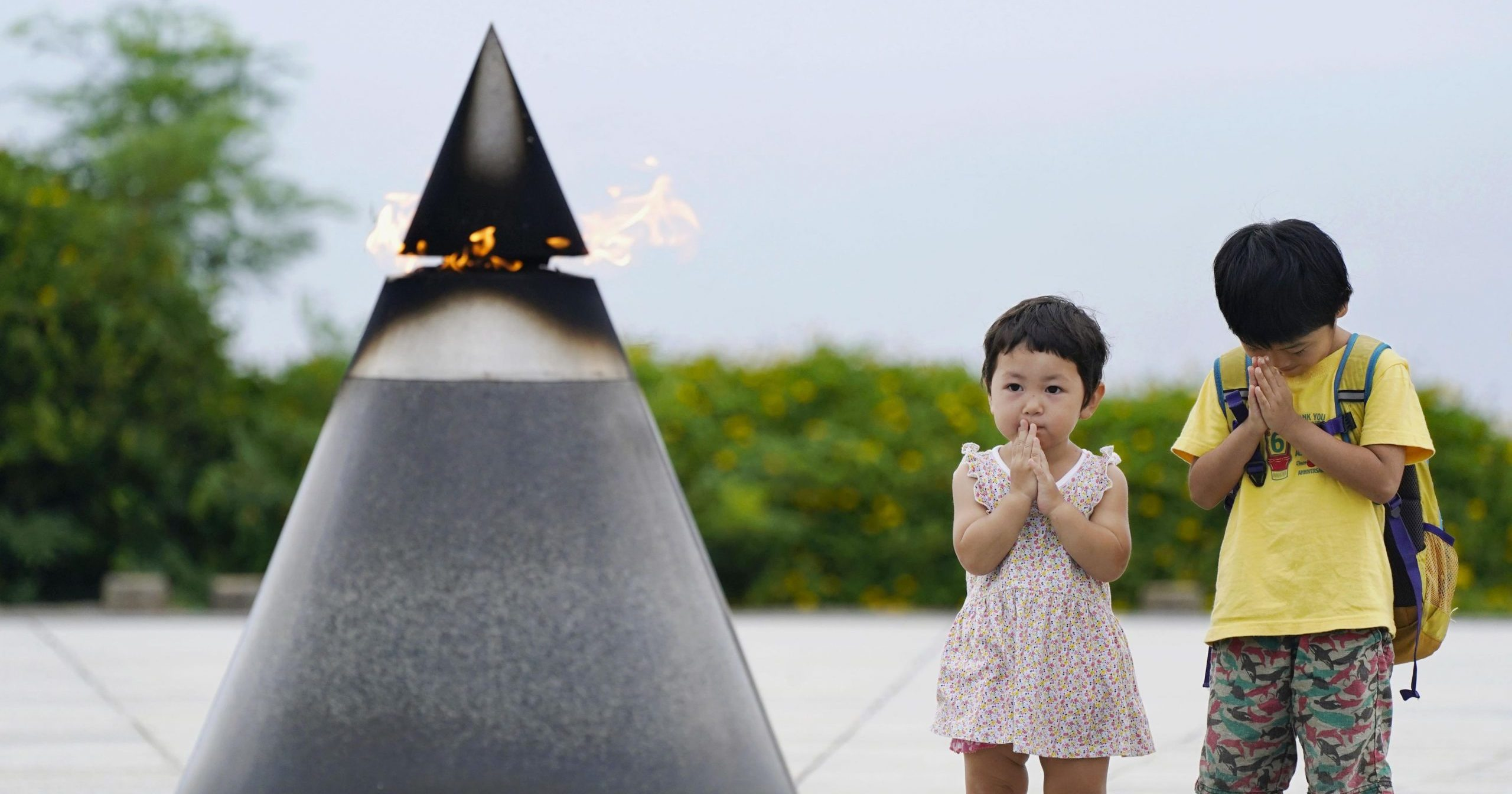 """Children pray in front of the """"Peace of Fire"""" at the Peace Memorial Park in Itoman, Okinawa, Japan, on June 23, 2020, 75 years after the Battle of Okinawa."""