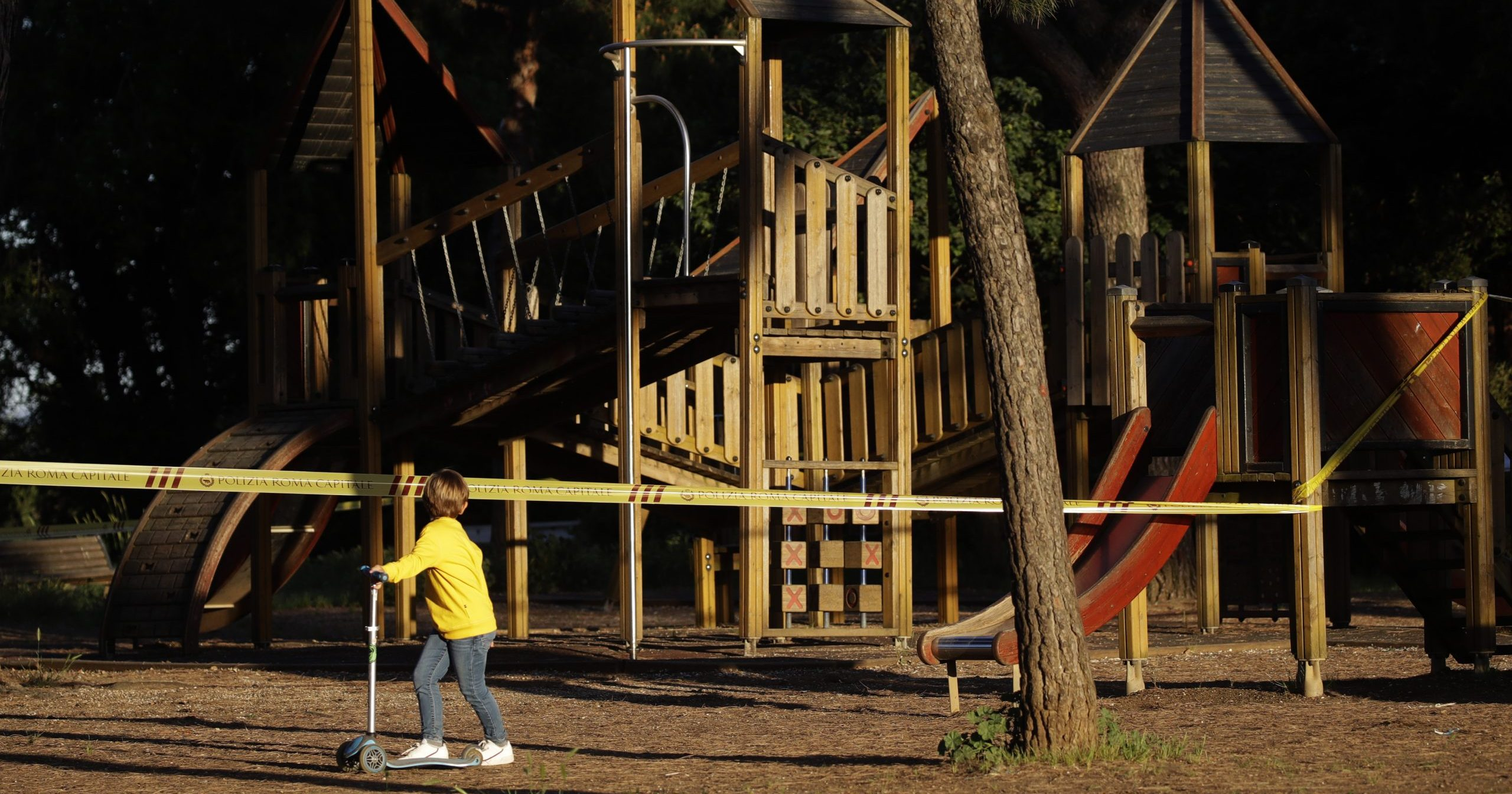 In this May 4, 2020, file photo, a child looks at a sealed-off playground at Rome's Villa Pamphili as the park reopened after several weeks of closure. A national survey of the psychological impact of coronavirus lockdowns on Italian children presented in Rome on June 16, 2020, has quantified what many parents noticed during weeks cooped up at home: Their kids were more irritable, had trouble sleeping, wept inconsolably and regressed developmentally.