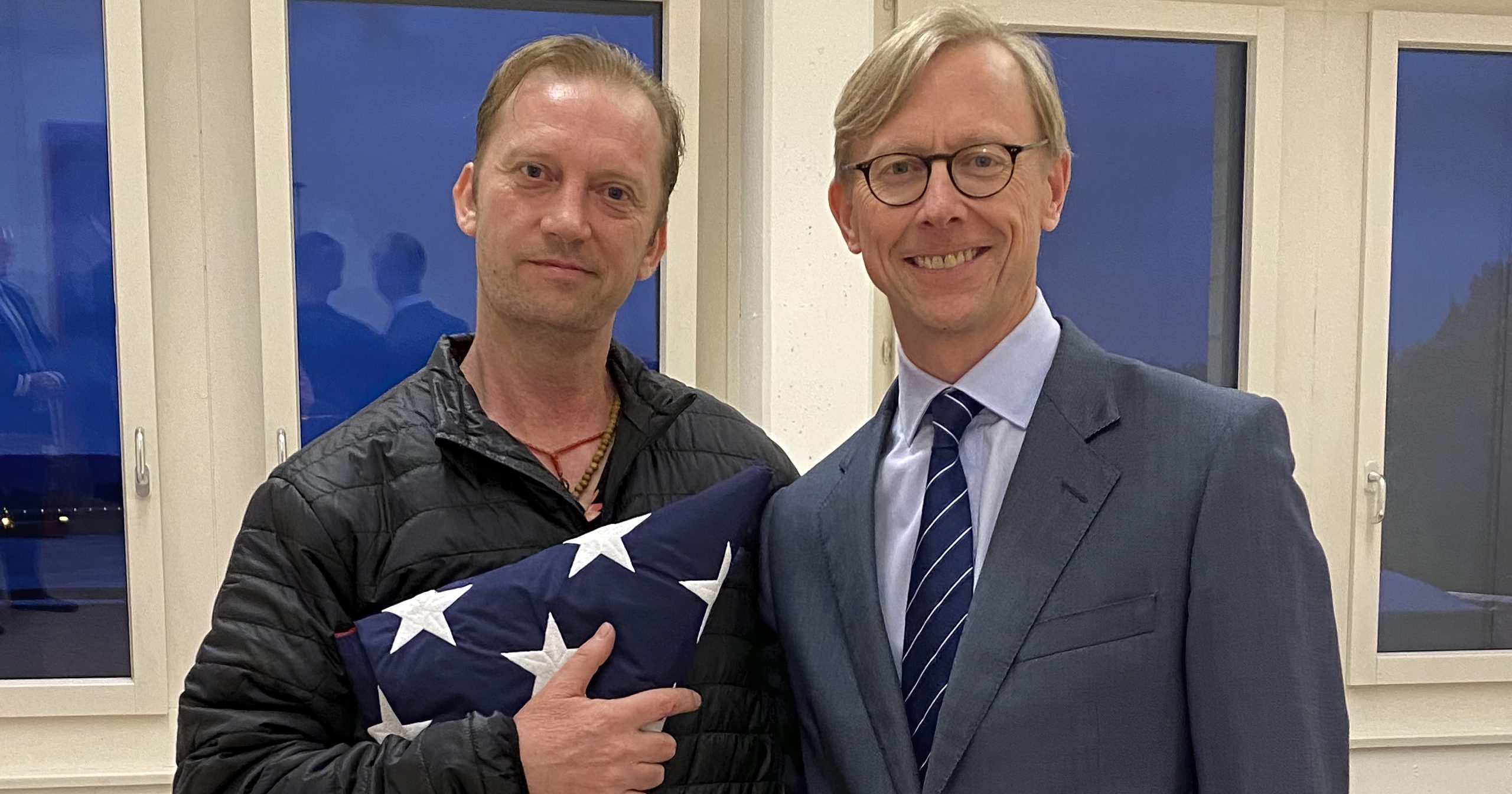 In this image provided by the U.S. State Department, Michael White holds an American flag as he poses for a photo on June 4, 2020, with U.S. special envoy for Iran Brian Hook at the Zurich, Switzerland, airport after White's release from Iran. White, a Navy veteran who's been detained in Iran for nearly two years, has been released and is making his way home.