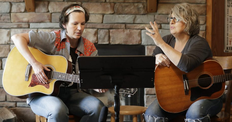 In this May 22, 2020, photo, nurse Megan Palmer, left, and care partner Anna Henderson, who both work at Vanderbilt University Medical Center, are seen during a songwriting session at Henderson's home in Ashland City, Tennessee. During the coronavirus pandemic, their role as caregivers has become even more important as hospital visits from family and friends are limited or prohibited.