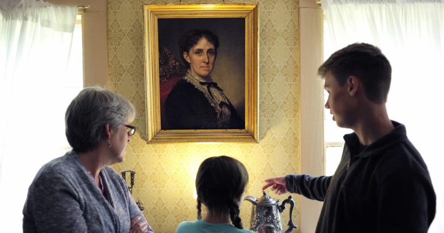 """In this May 17, 2018, file photo, museum visitors stand near a portrait of author Louisa May Alcott at Orchard House in Concord, Massachusetts. The current issue of The Strand Magazine will give readers the chance to discover an obscure and unfinished work of fiction by Alcott, """"Aunt Nellie's Diary,"""" and to provide a conclusion themselves."""