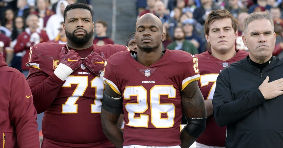In this Dec. 22, 2018, file photo, Washington Redskins running back Adrian Peterson (26) stands for the national anthem before an NFL football game against the Tennessee Titans in Nashville.