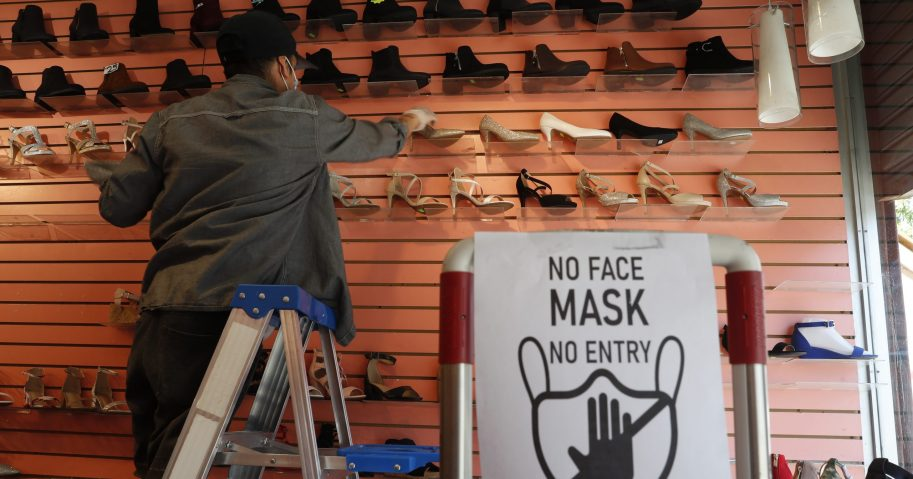 Manager Angel Ramos arranges shoes on a display in Top Shoes in the Brooklyn borough of New York on, June 8, 2020.