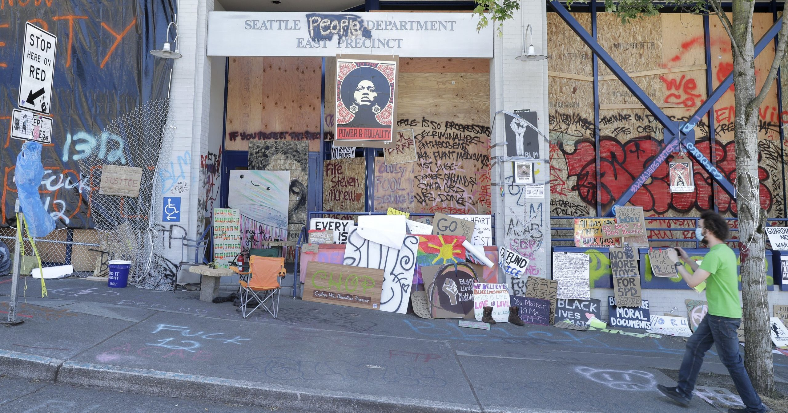 """A person takes a photo of the Seattle Police East Precinct building on June 22, 2020, inside what has been named the Capitol Hill Occupied Protest zone in Seattle. For the second time in less than 48 hours, there was a shooting near the """"CHOP"""" area that has been occupied by protesters after police pulled back from several blocks of the city's Capitol Hill neighborhood."""