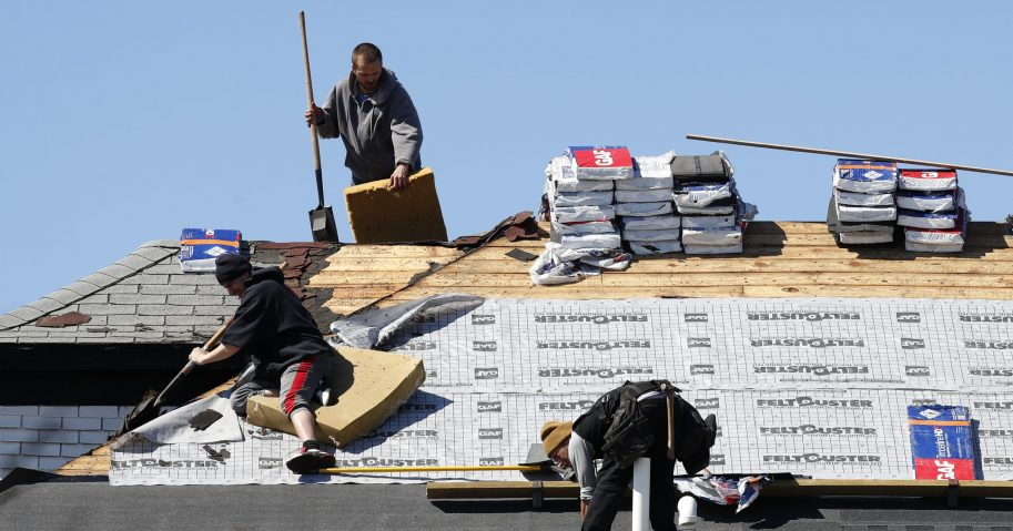 In this Apr. 2, 2020, file photo, roofers work on removing and placing new shingles in Warren, Michigan. U.S. home-building activity collapsed in March, but a June 17 Commerce Department report indicates recovery in May.