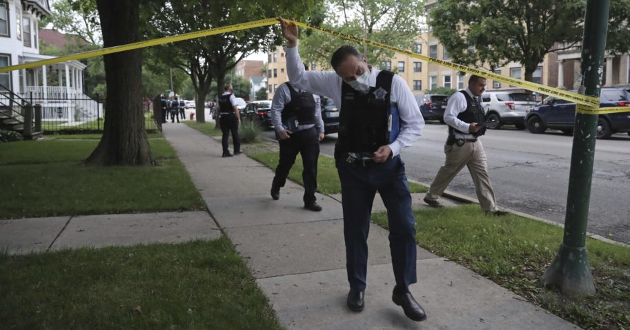 Police detectives canvas the area where a 3-year-old boy was fatally shot while riding in an SUV with his father on June 20, 2020, in Chicago. More than 100 people were shot in a wave of gunfire in Chicago over the Father's Day weekend that produced the city's highest number of shooting victims in a single weekend this year.