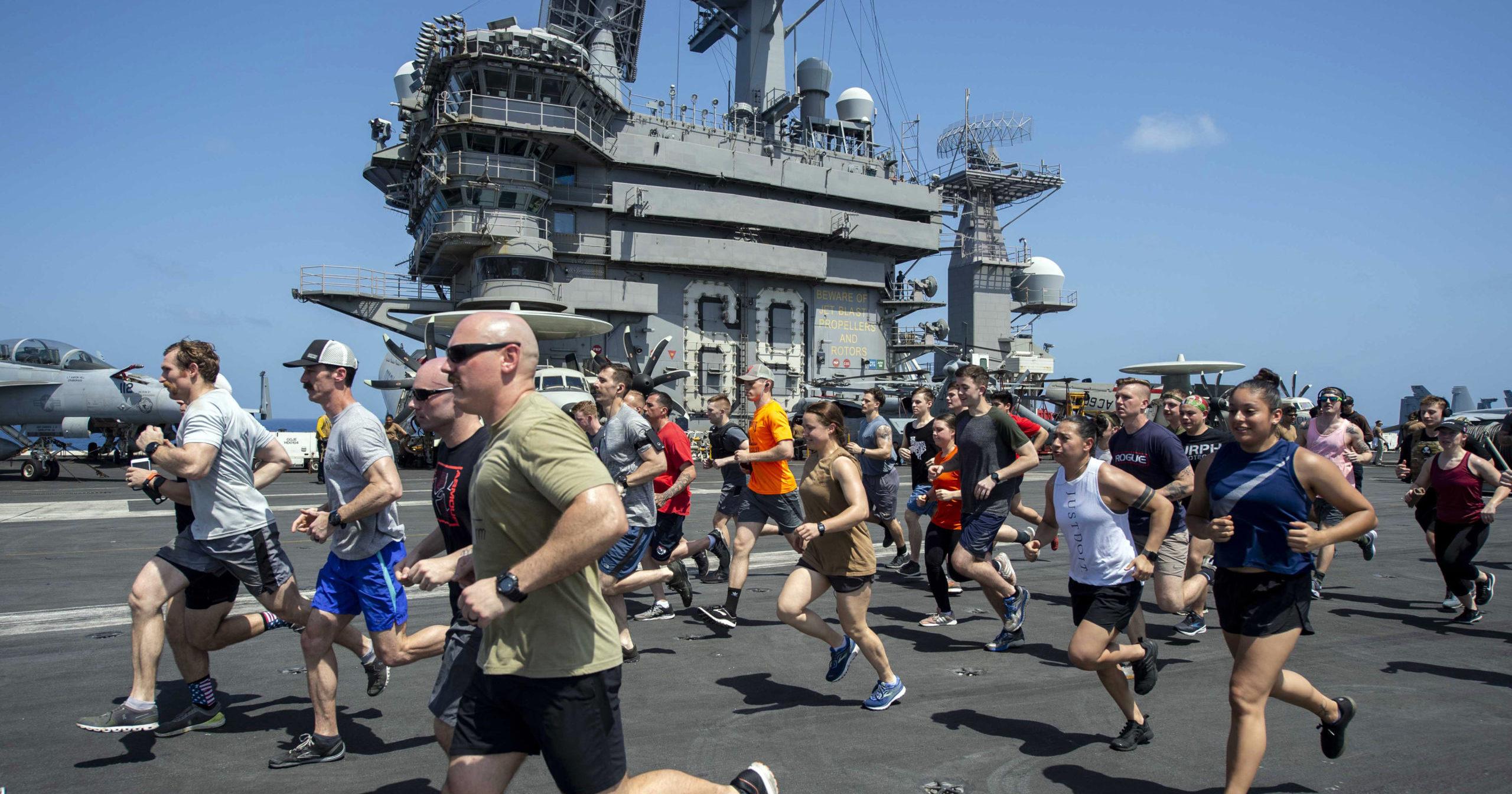 Sailors run on the flight deck of the aircraft carrier USS Dwight D. Eisenhower on May 24, 2020.