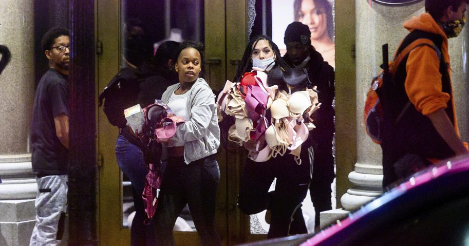 In this May 30, 2020, file photo, women carry merchandise from a Union Square Victoria's Secret store in San Francisco. Police say many of the smash-and-grab thefts have been carried out by caravans of well-coordinated criminals and have coincided with or followed protests over the death of George Floyd.