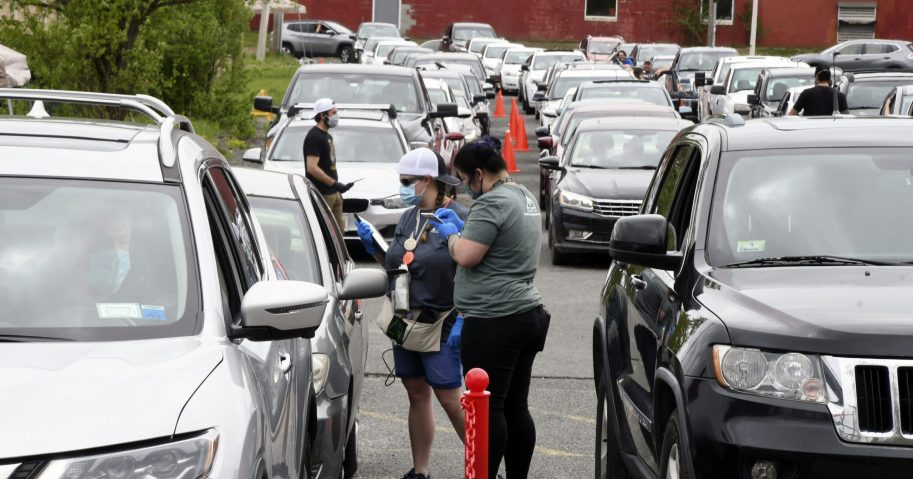 Amanda Toma and Ashley Brodeur work with customers in the parking lot of cannabis purveyor Berkshire Roots in Pittsfield, Massachusetts, on May 25, 2020.