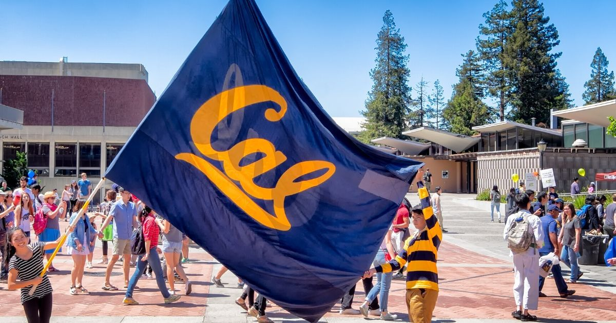 University students raise a large school flag in a show of school spirit on Cal Day, an annual campus open house for students, alumni and community visitors, at the University of California, Berkeley.