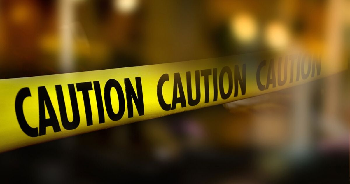 Caution tape and a blurred law enforcement and forensic background are seen in the image above.