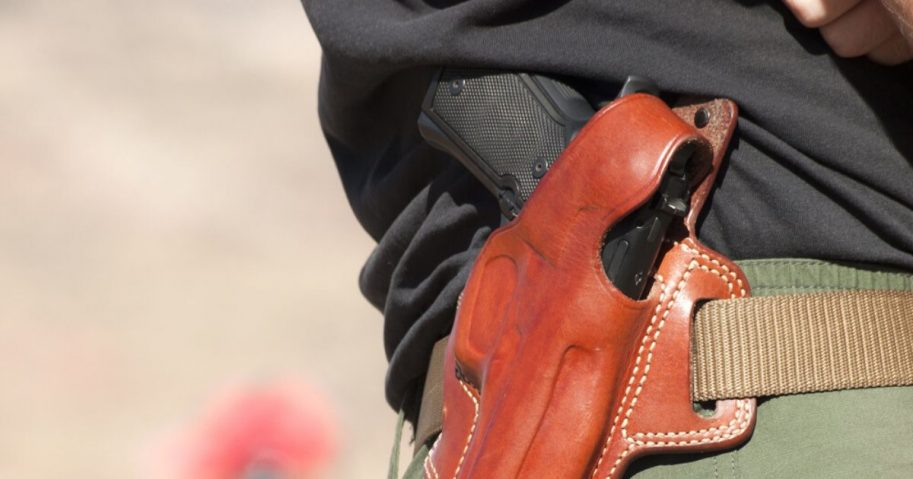 A gun is seen in a holster in the stock image above.