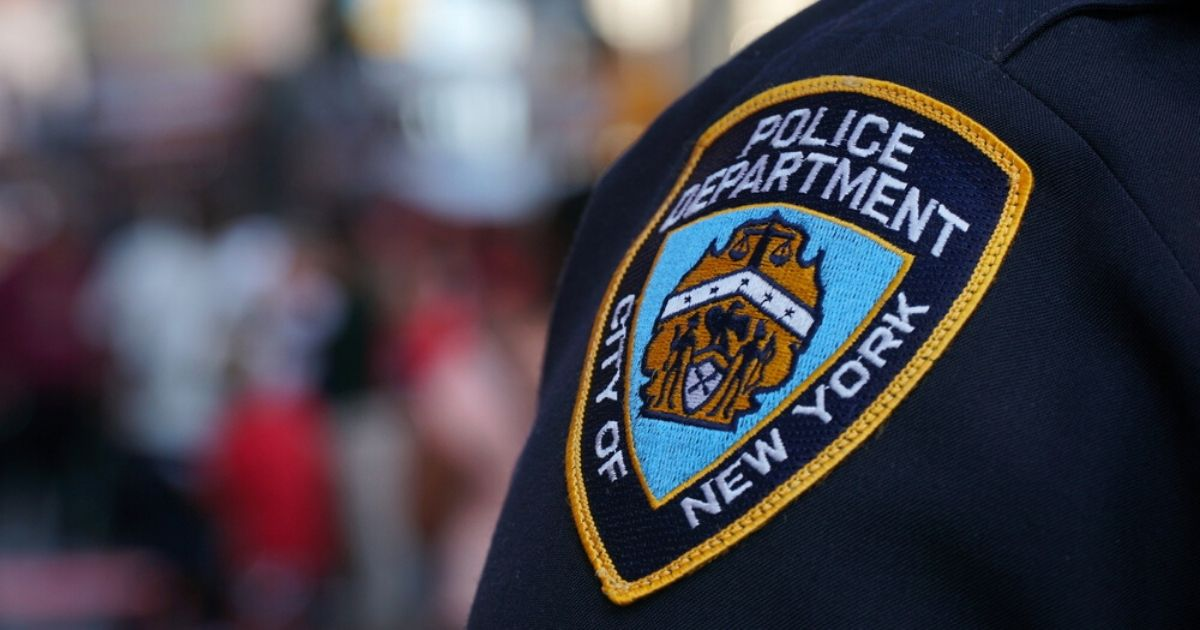 A stock photo of an NYPD badge is seen above.