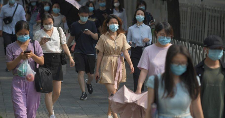 People wear masks as they walk to work in Beijing on June 28, 2020.