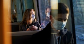 People wear face masks on a train in the stock image above.