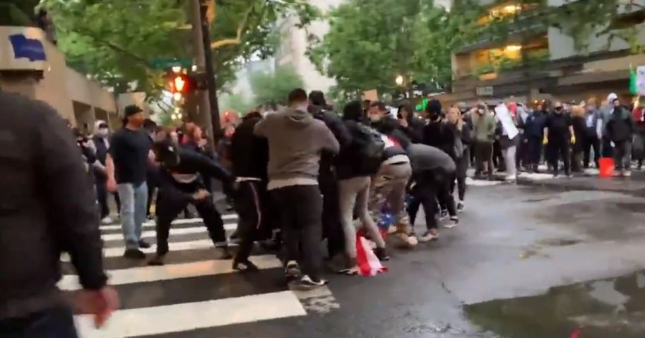 Rioters in Portland, Oregon, swarm a man clinging to an American flag.
