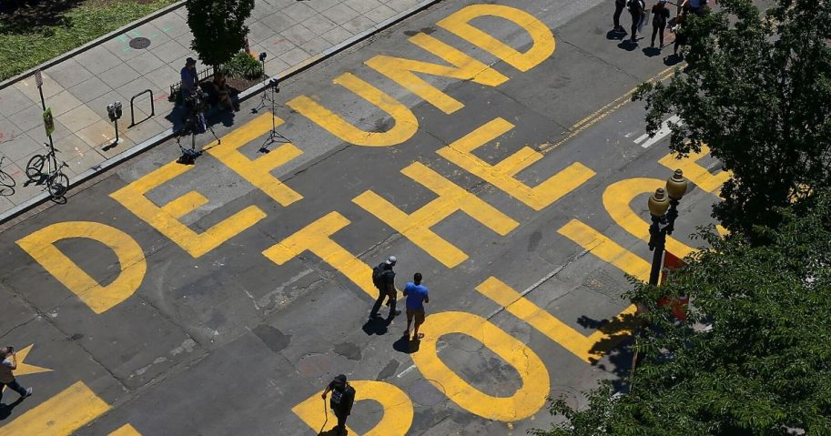 "People walk down 16th Street after ""Defund The Police"" was painted on the street near the White House on June 8, 2020, in Washington, D.C."