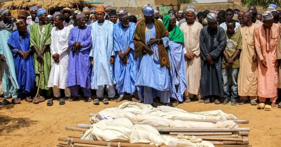 Men pray next to coffins during a burial ceremony after two people were killed by Boko Haram terrorists near Maiduguri, Nigeria, on July 26, 2019.