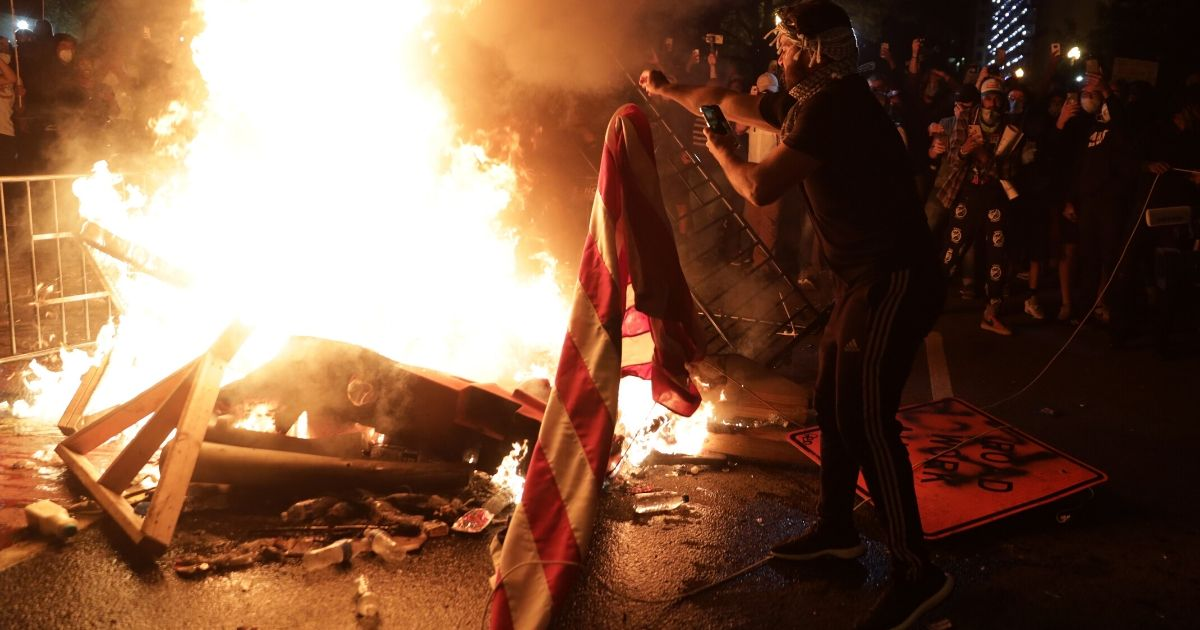 Rioters set a fire and burn a U.S. flag near the White House on May 31, 2020, in Washington, D.C.