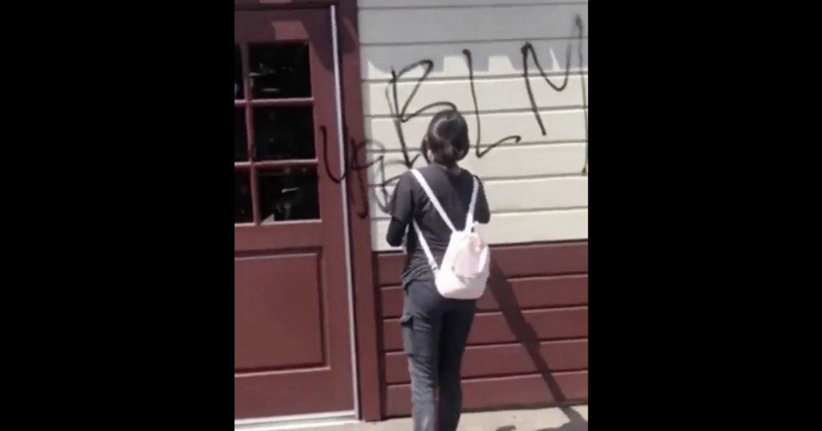 A black woman confronts two masked white women defacing a Starbucks.