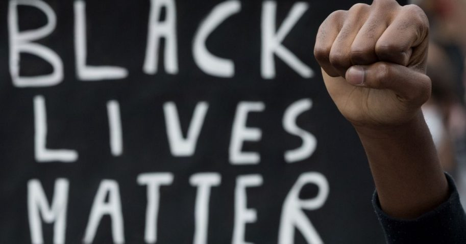 "A protester raises a fist next to a placard in Nantes, France, on June 8, 2020, during a ""Black Lives Matter"" protest."