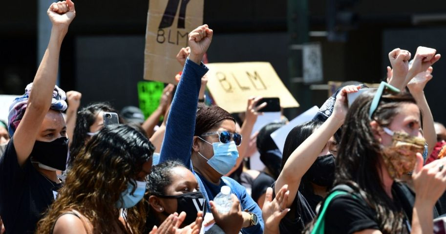 People hold up their fists during a memorial service honoring George Floyd in downtown Los Angeles on June 8, 2020.