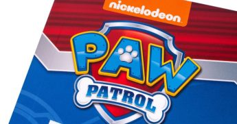 """A close-up of the """"Paw Patrol"""" logo on the front cover of a children's book."""