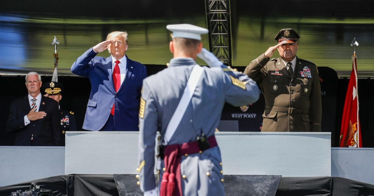 President Donald Trump, left, and United States Military Academy Superintendent Darryl A. Williams, right, salute graduating cadets Saturday at West Point.