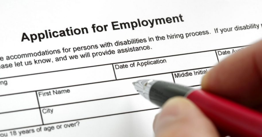 Stock image of a person filling out a job application form.