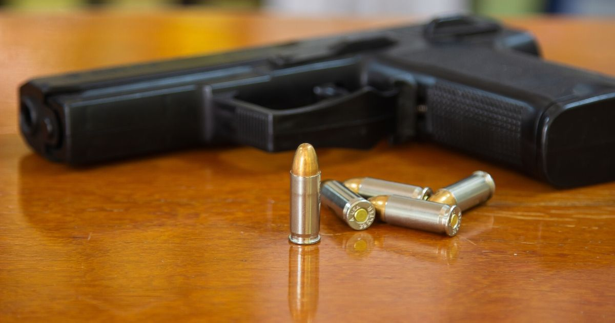 A handgun and bullets rest on a wooden table.