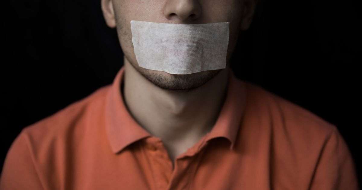 Stock image of a man with adhesive tape on his mouth.