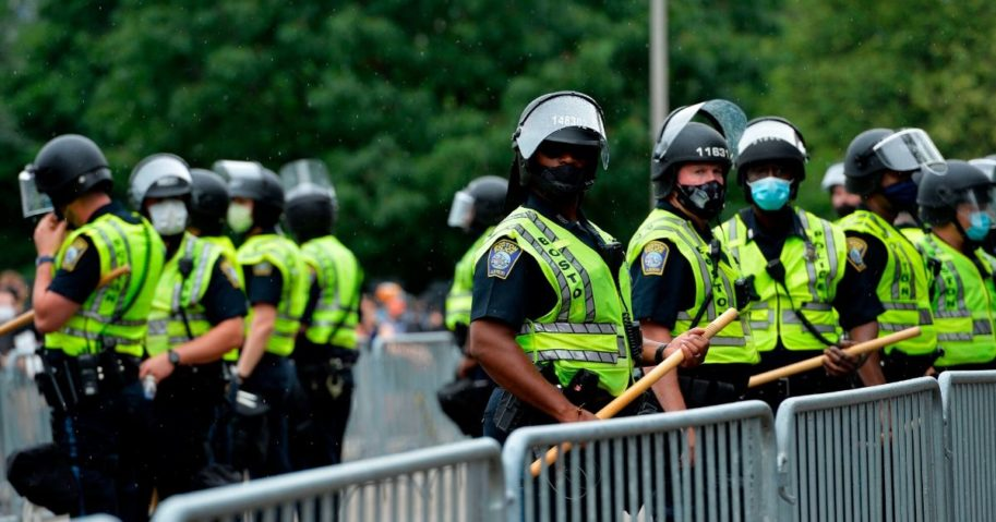 Police officers in riot gear stand guard outside the State House in Boston on June 27, 2020.