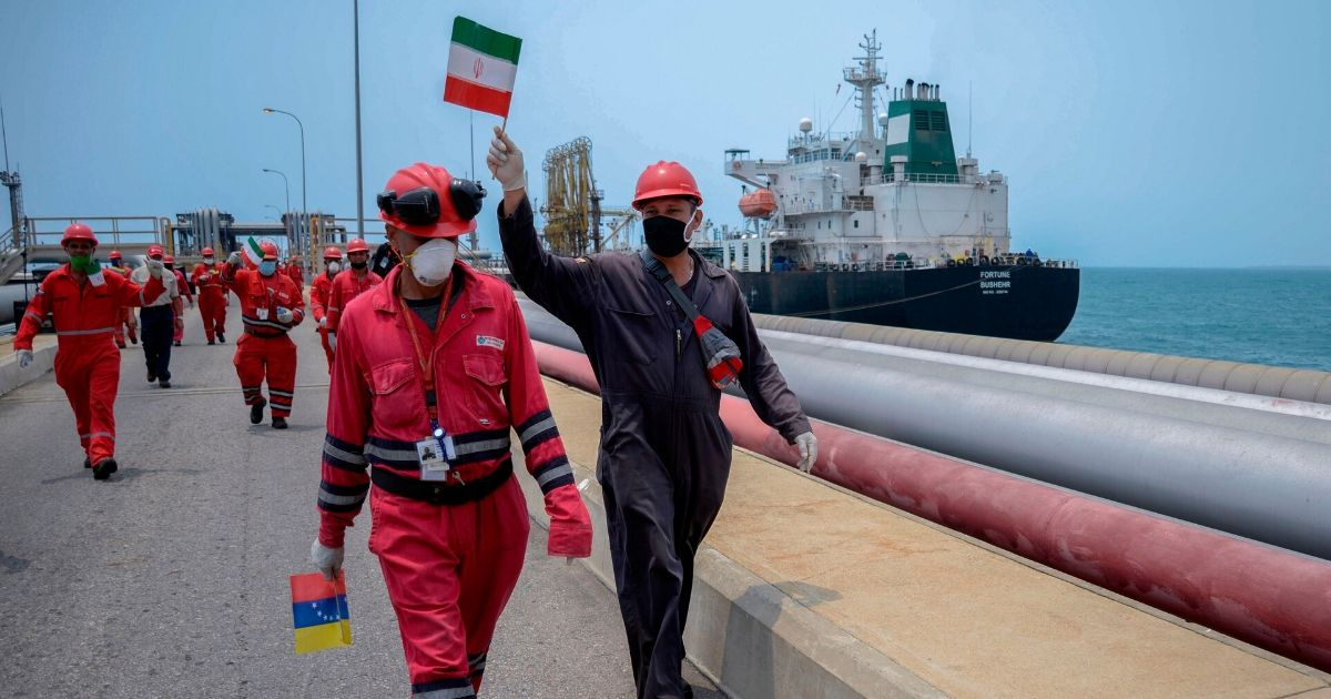 A worker of the Venezuelan state oil company PDVSA waves an Iranian flag