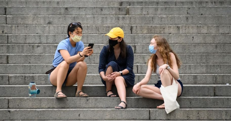 Young women wearing protective face masks sit on the steps of the Metropolitan Museum of Art in New York on May 30, 2020.