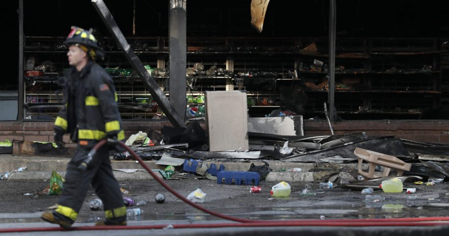 A member of the St. Louis Fire Department wraps up his work outside a vandalized and burned convenience store on Tuesday, June 2, 2020, in St. Louis. On Monday night people were seen removing items from the store before the building went up in flames after a large peaceful protest of the death of George Floyd had ended.