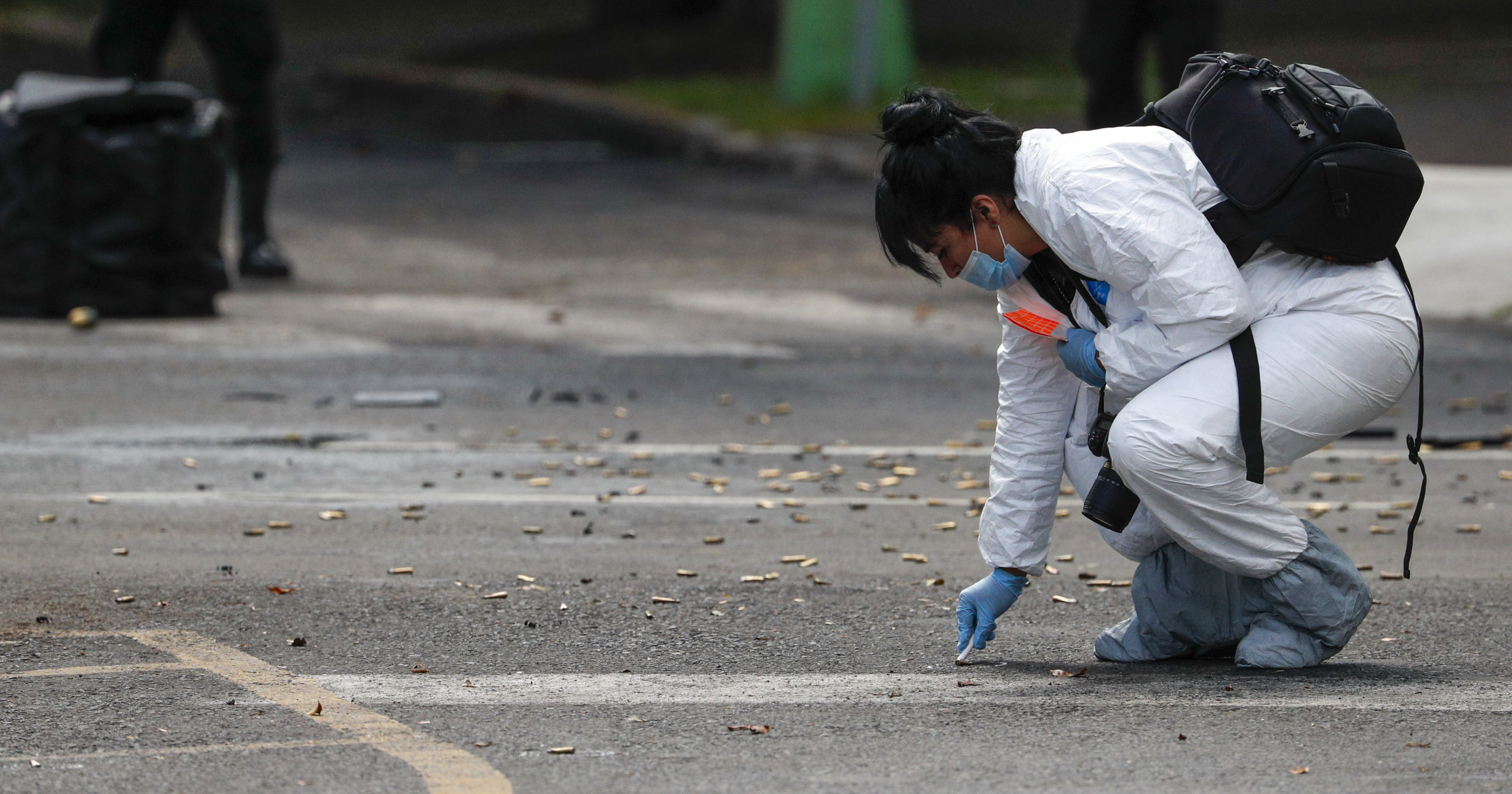 A forensic investigator collects cartridges at the scene where Mexico City's police chief was attacked by gunmen on June 26, 2020. Heavily armed gunmen attacked and wounded Omar García Harfuch in an operation that left three dead.