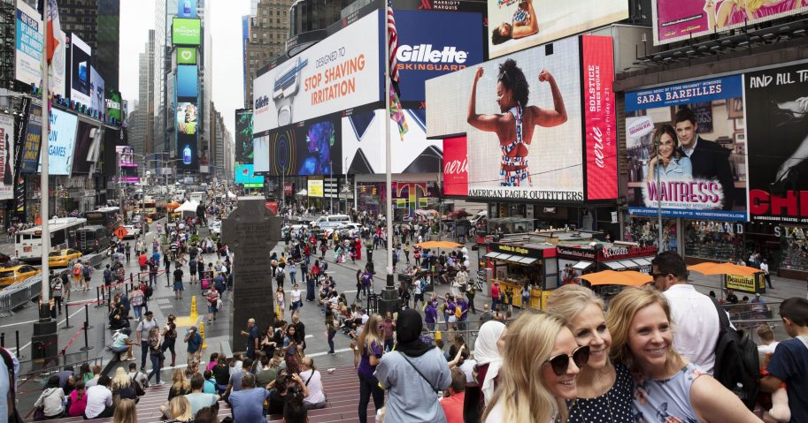 In this June 20, 2019, file photo, tourists visit Times Square in New York. After three months of a coronavirus crisis followed by protests and unrest, New York City is trying to turn a page as a limited range of industries reopen Monday, June 8, 2020.