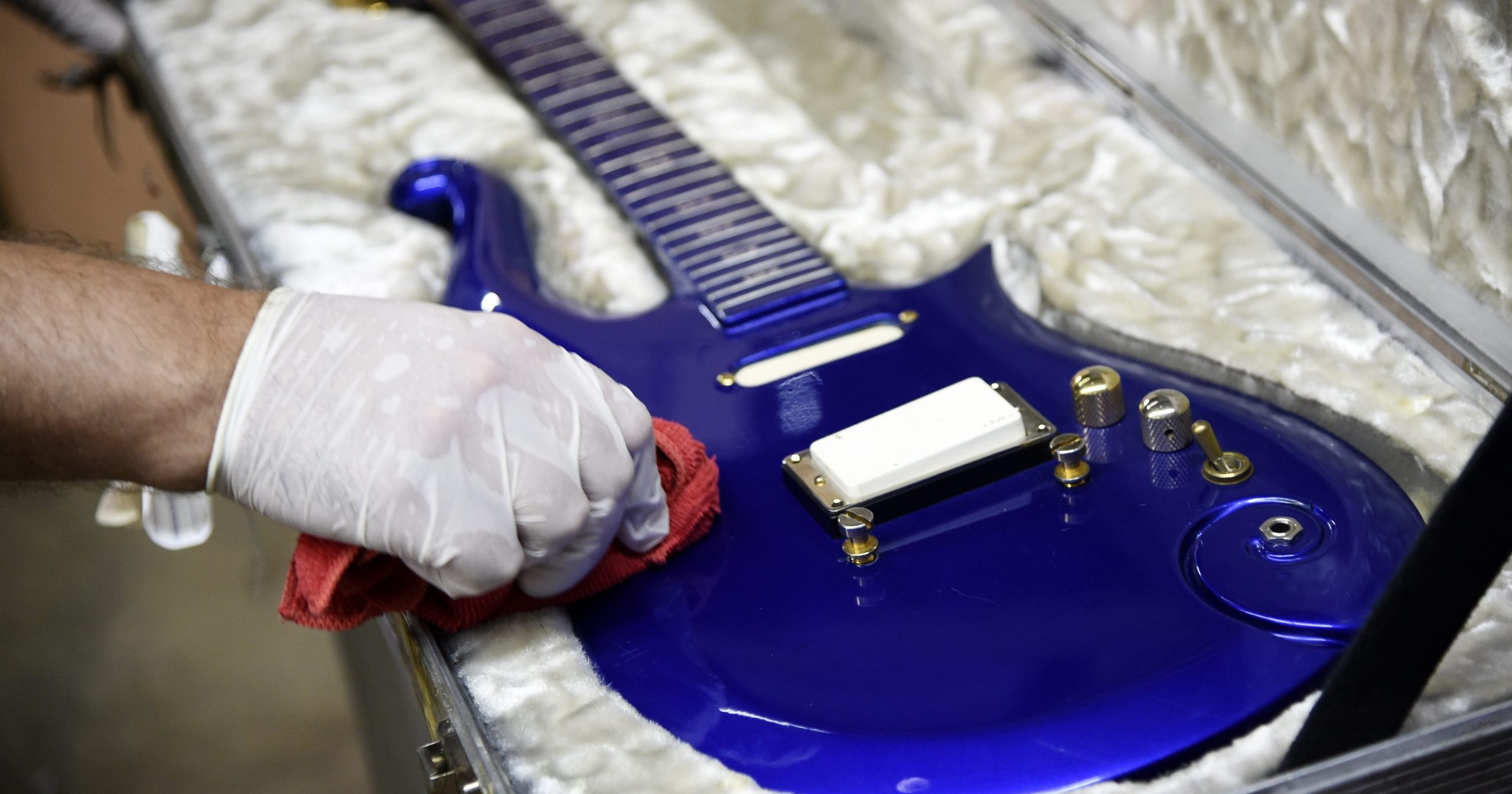 """In this May 6, 2020, file photo, the """"Blue Angel"""" Cloud 2 electric guitar custom-made for the musician Prince in the 1980s is polished at Julien's Auctions warehouse in Culver City, California. On June 19, 2020, the instrument shot past the top estimate of $200,000 it was expected to fetch at the Music Icons sale at the auction house."""