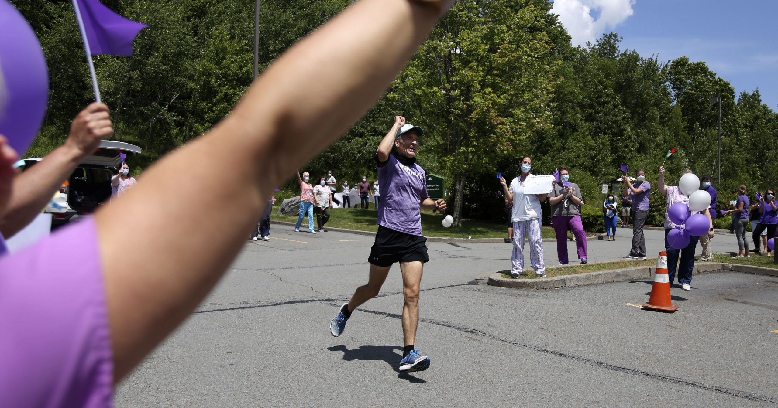 Nursing home workers cheer as Corey Cappelloni completes his seventh ultramarathon in seven days in Scranton, Pennsylvania, on June 19, 2020. Cappelloni ran roughly 218 miles from Washington, D.C., to Scranton to visit his 98-year-old grandmother and raise awareness for patients in isolation amid the coronavirus pandemic.