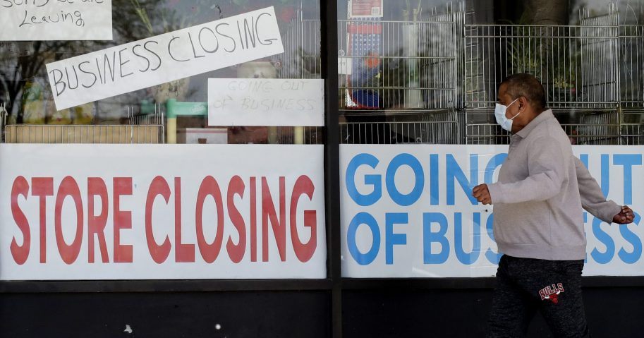In this May 21, 2020 file photo, a man looks at signs of a closed store in Niles, Illinois. U.S. businesses shed 2.76 million jobs in May, as the economic damage from the coronavirus shutdowns stretched into a third month.