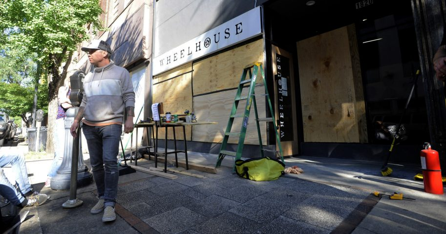 Owner Johnny Grimes stands outside his salon on June 1, 2020, in Birmingham, Alabama, as he works to board up the windows after it was vandalized and looted.