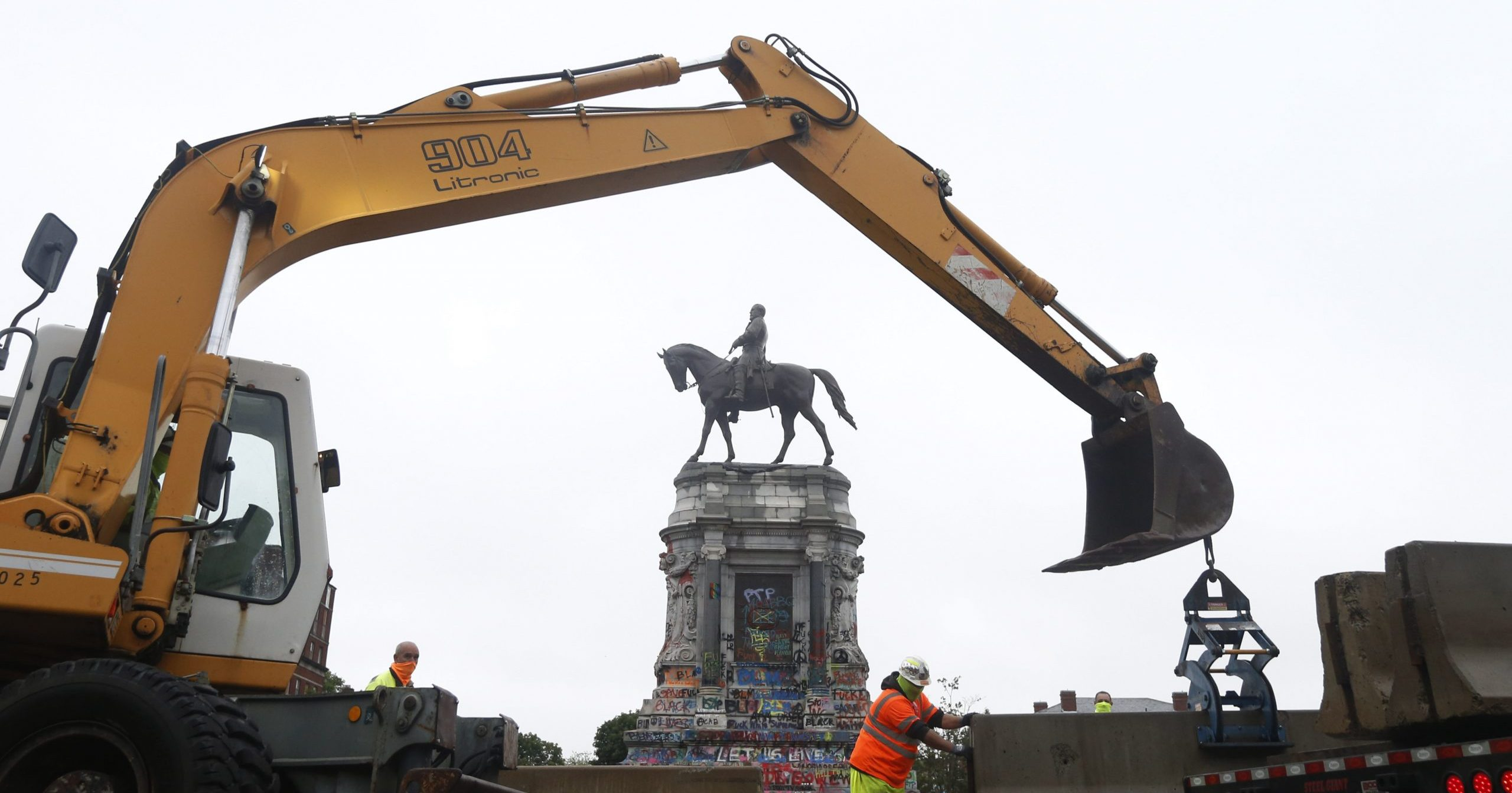 Workers for the Virginia Department of General Services install protective concrete barriers around the statue of Confederate General Robert E. Lee on Monument Avenue on June 17, 2020, in Richmond, Virginia.