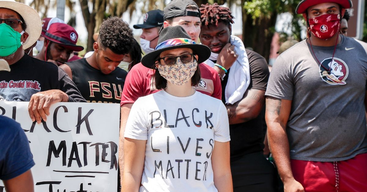 Protesters join in a march led by the Florida State football team on June 13, 2020, in Tallahassee, Florida, in support of the Black Lives Matter movement.