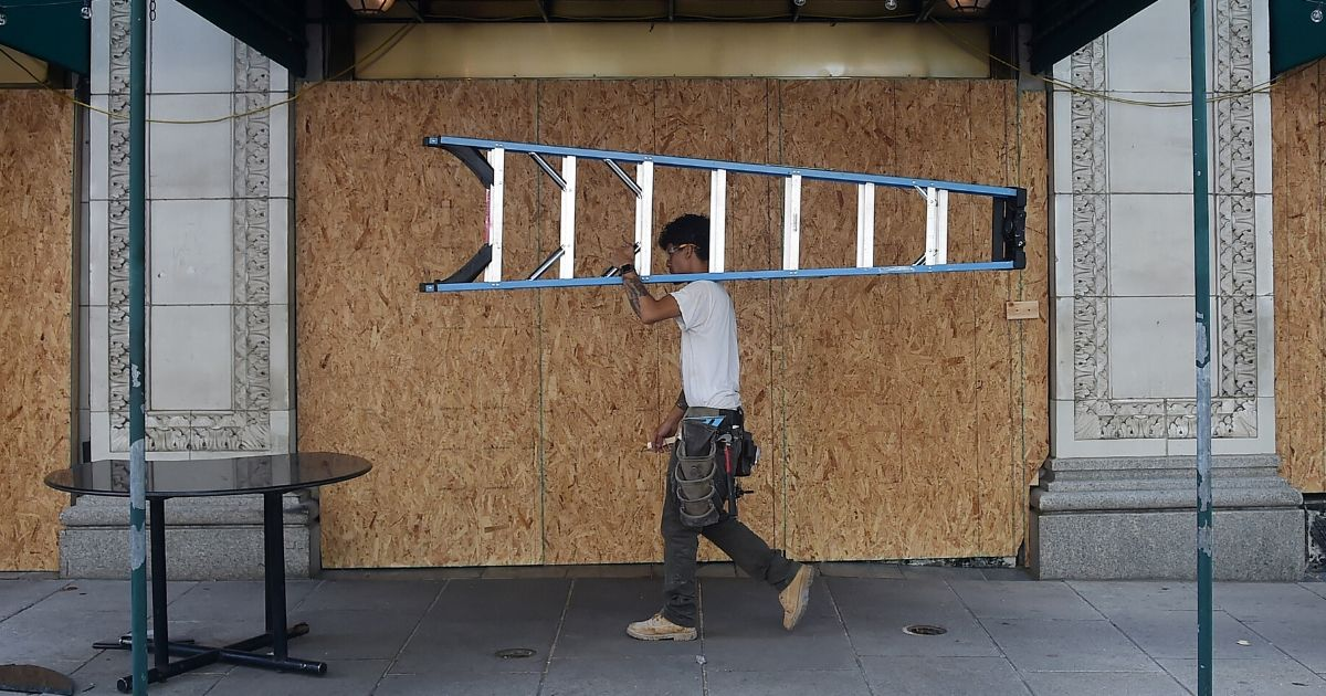 A worker carrying a ladder walks past a boarded up restaurant on June 19, 2020, in Washington, D.C.