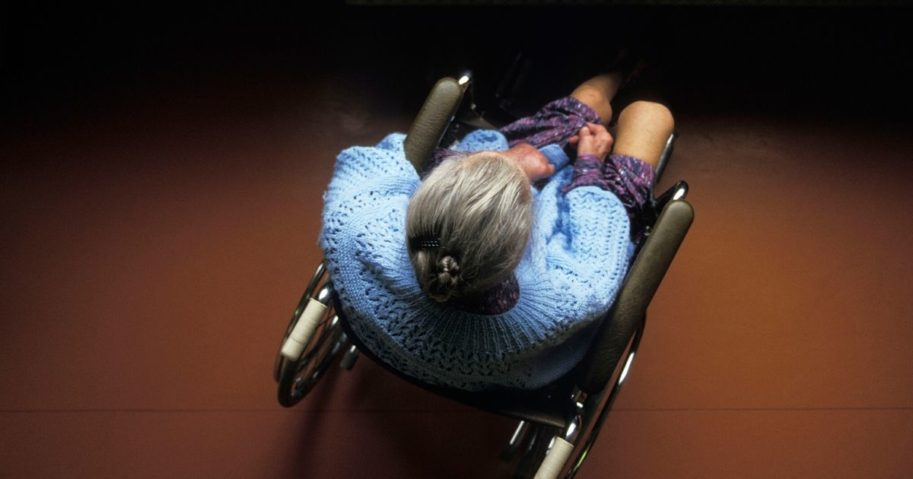 An elderly woman sits in a wheelchair.