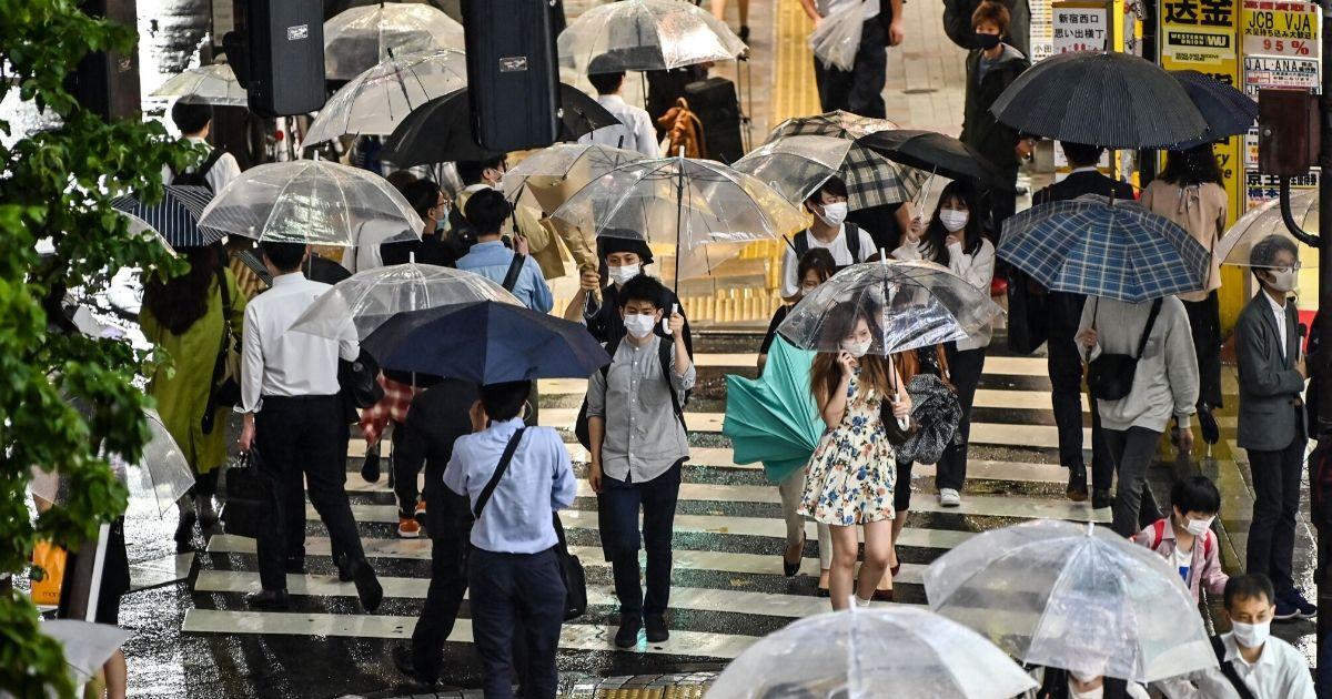 Pedestrians walk with umbrellas as evening rain falls in Tokyo on June 19, 2020.